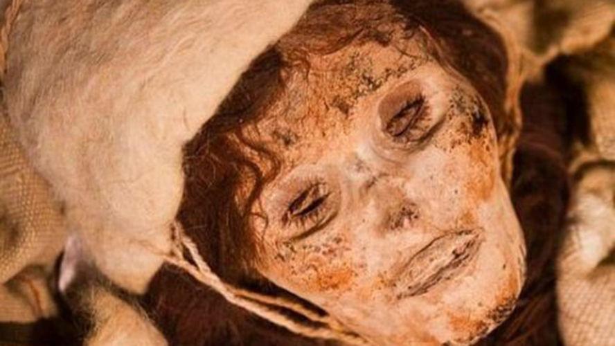 O cílios longos nos olhos semiabertos e os cabelos longos ainda em excelente estado caem sobre os ombros da múmia de 3800 anos.