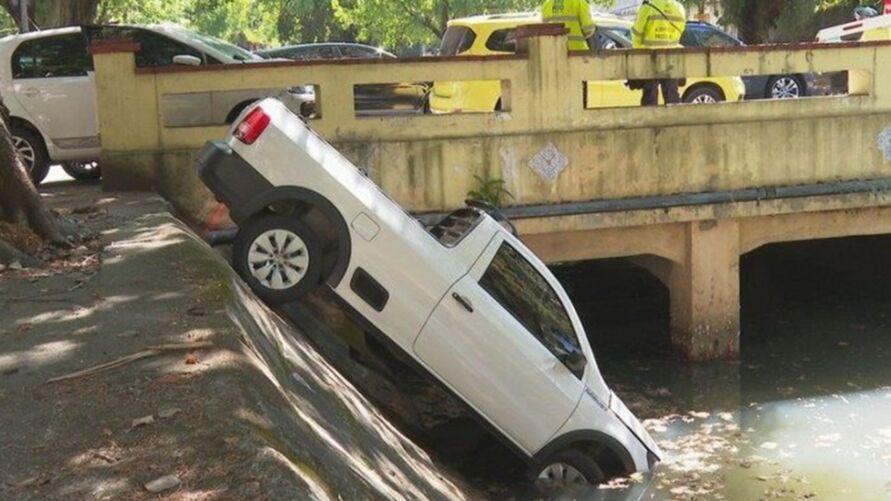 Carro bate e cai em canal