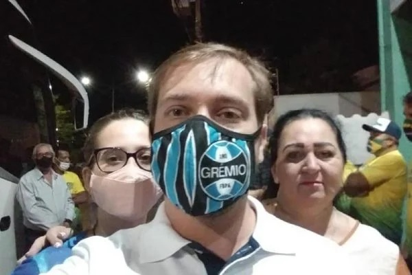 A servidora aparece sem máscara (ela está à direita do homem com máscara do Grêmio na imagem em destaque).