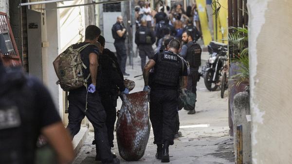 Policiais carregando os corpos durante a operação