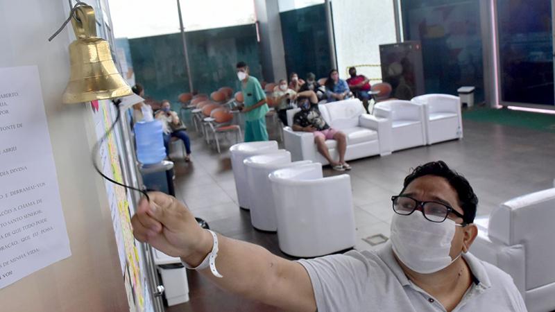 Paciente toca o sino ao receber alta do hospital de campanha, no Hangar