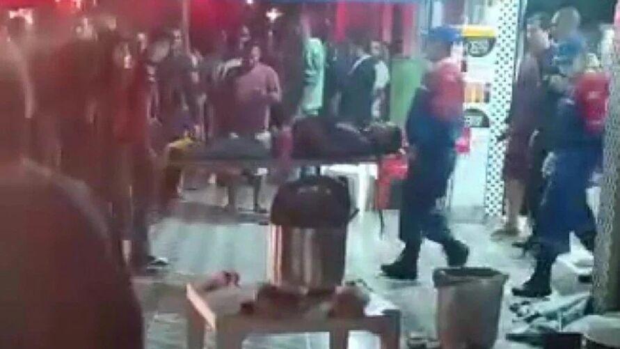 Vítimas estavam assistindo jogo no bar, quando criminosos passaram em um carro já atirando.