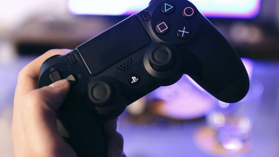Pessoa segurando um controle de PS4