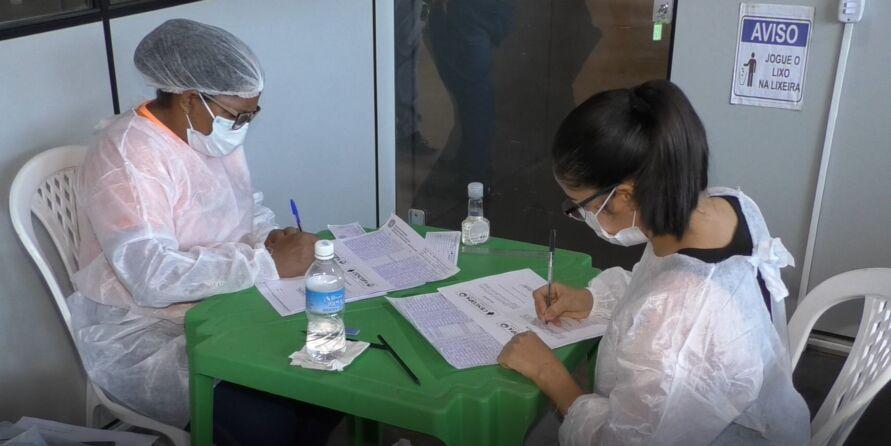 Profissionais da saúde preenchendo carteiras de vacinação.