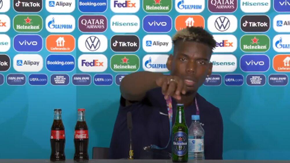 Pogba faz igual Cristiano Ronaldo e tira uma garrafa de cerveja de cima da mesa, em entrevista coletiva.