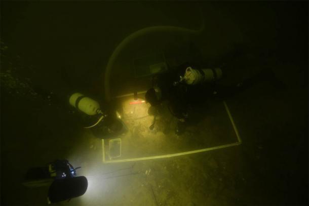 Arqueólogos subaquáticos examinando os artefatos no Lago Asveja, Lituânia