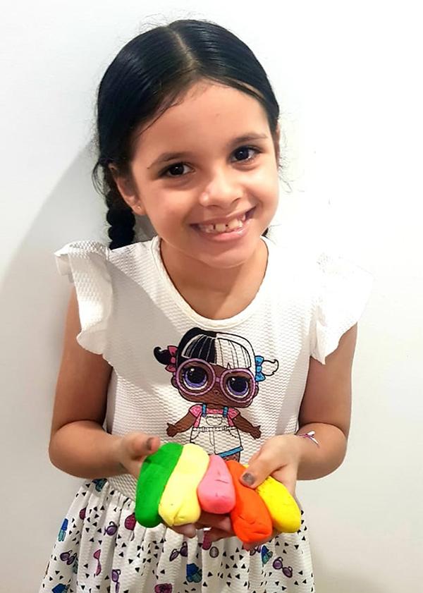 Gabriella Ribeiro, de 7 anos, mostra as massinhas que fez em casa.