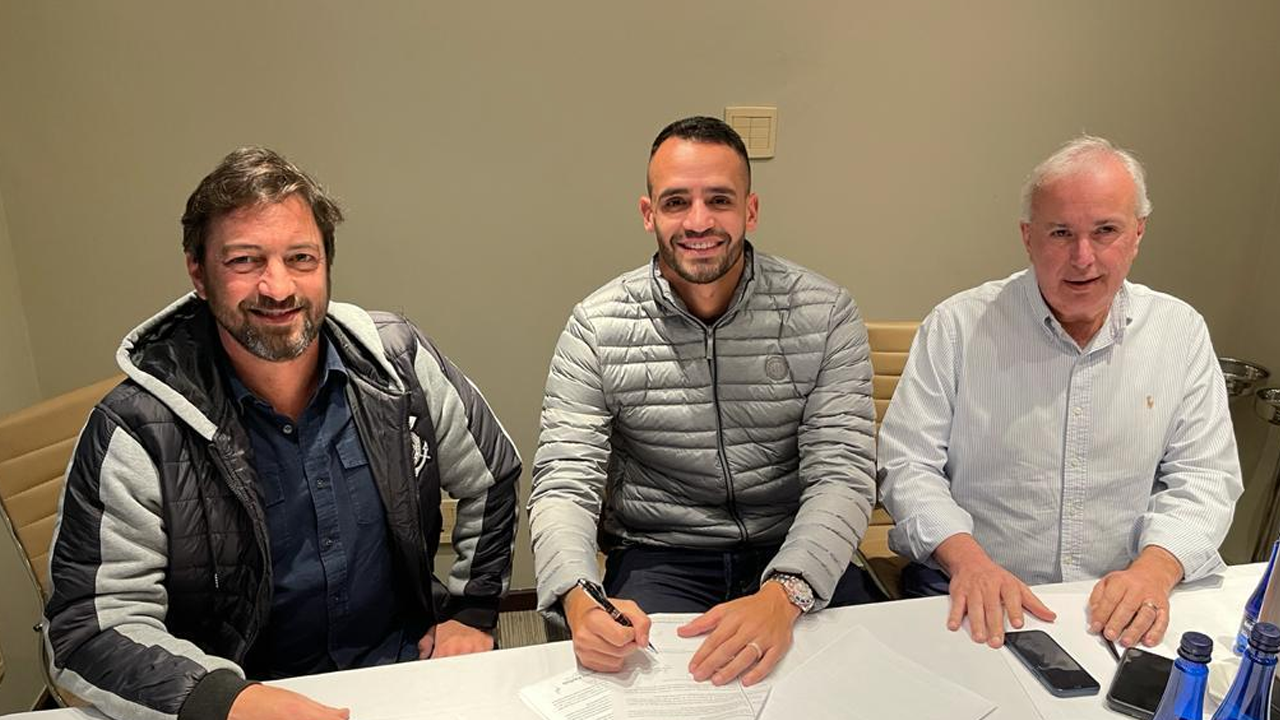 Renato Augusto no momento em que está assinando o contrato.